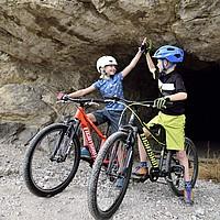 """Ein Junge und ein Mädchen sind vom Fahrrad abgestiegen und geben sich ein """"high five""""."""