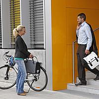 Eine Frau kommt mit dem Fahrrad an ihrer Arbeitsstelle an. Ein Mann kommt aus dem Gebäude und kommt ihr auf einer Treppe entgegegen. Beide lächeln sich an.