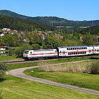 Intercity fährt durch eine grüne Landschaft