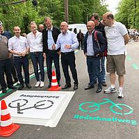 """Minister Hermann steht mit einer Gruppe von Menschen auf dem Radschnellweg, auf dem Boden sieht man die grüne """"Radschnellweg""""-Kennzeichnung."""