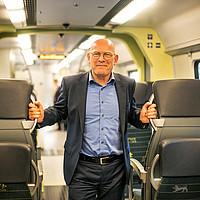 Verkehrsminister Hermann posiert lächelnd im Gang eines Zugs.