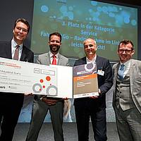 Bei der Preisverleihung wird Vertretern des Rems-Murr-Kreises ein symbolischer Scheck über 1000 Euro verliehen.