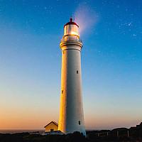 Strahlender Leuchtturm vor einem klaren Abendhimmel.