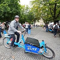 Verkehrsminister Hermann fährt auf einem blauen Lastenrad