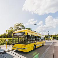 Ein gelber Elektrobus an einer Haltestelle in Berlin, darüber blauer Himmel mit weißen Wolken