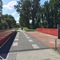 Ein Radweg führt über eine Brücke in eine Landschaft mit Bäumen. In der Ferne sehen wir zwei Radfahrer mit Helmen von hinten.