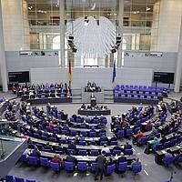Plenarsitzung im Bundestag. Man sieht das Halbrund von Hinten, über dem Rednerpult hängt der Bundesadler.