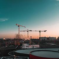 Silhouette von Baukränen über einer abendlichen Stadt