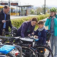 Eine Familie mit zwei Kindern schließt ihre Fahrräder an einer Abstellanlage an. Im Hintergrund sieht man eine Straßenbahnhaltestelle.