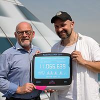 Minister Hermann und Dodokay halten eine elektronische Tafel in die Kamera, auf der die Zahl der gefahrenen Kilometer zu sehen ist.