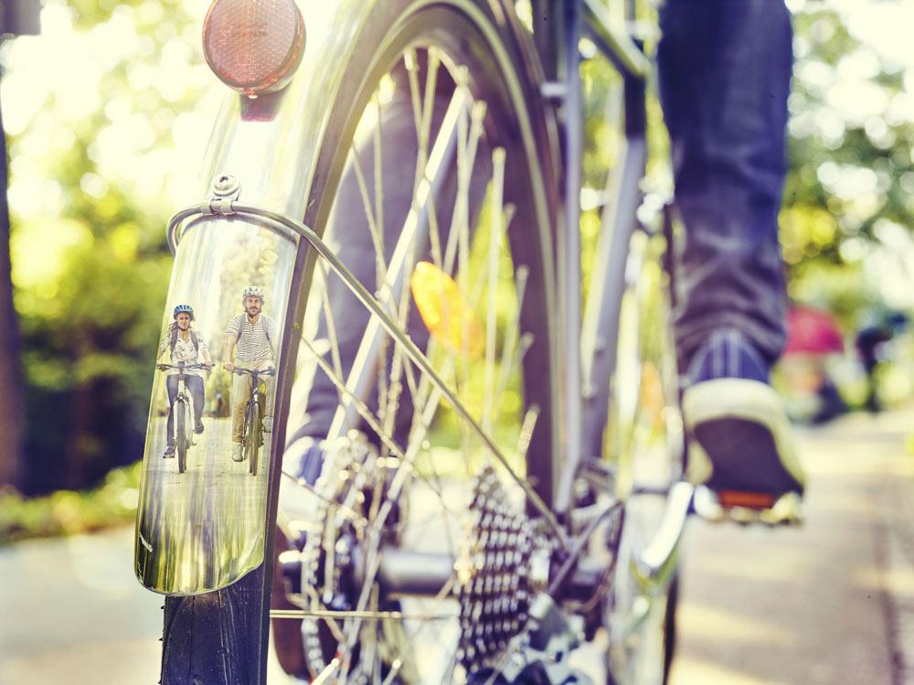 Bild zeigt das hintere Schutzblech eines Fahrades samt sich darin spiegelender Radfahrender